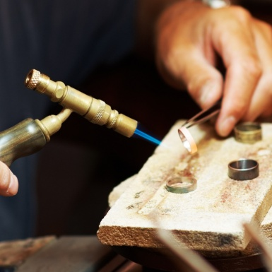 Jeweler using a blowtorch while he works on a ring